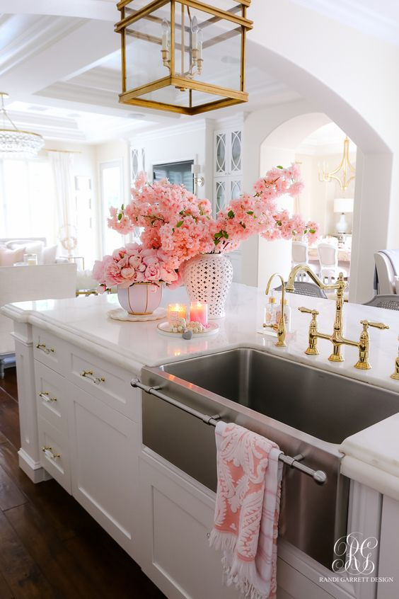 a glam white kitchen with shaker cabinets, gold handles, a gold pendant lamp and fixutres paired up with a chromatic sink