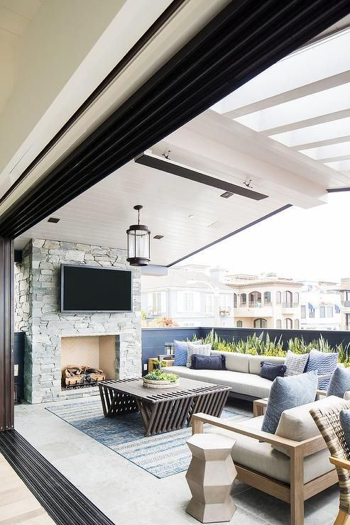 a gorgeous balcony with a stone fireplace, neutral furniture, a dark stained coffee tables, blue printed textiles and lots of greenery