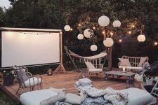 a gorgeous boho outdoor moovie space with rattan furniture, some mattresses, a movie screen and paper lamps plus lights