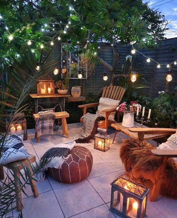 a gorgeous boho outdoor space with wooden furniture, candle lanterns, string lights, lots of greenery and a tree and printed boho blankets