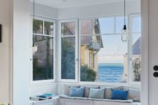a gorgeous bow window with an upholstered built-in bench and a fantastic view of the sea is amazing