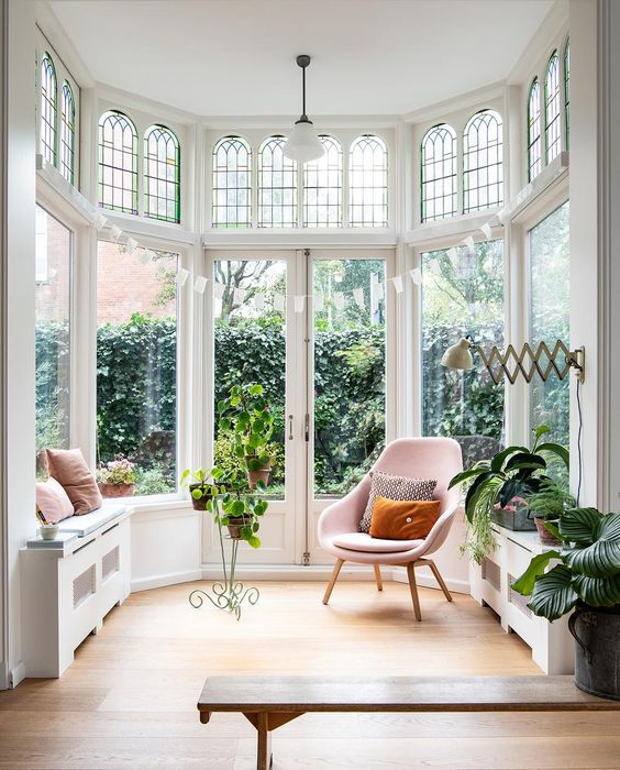 a gorgeous bow window with doors to the garden, with mosaic framing over them, potted greenery, a pink chair is a fantastic space