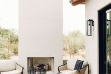 a gorgeous  contemporary outdoor space with a fireplace, some wood and metal furniture and neutral upholstery is extremely welcoming and cozy