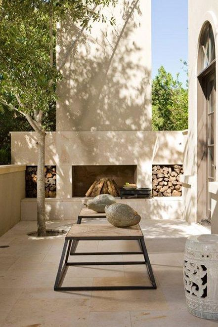 a gorgeous contemporary terrace clad with tiles, a fireplace and firewood storage, wooden benches, a living tree right in the center
