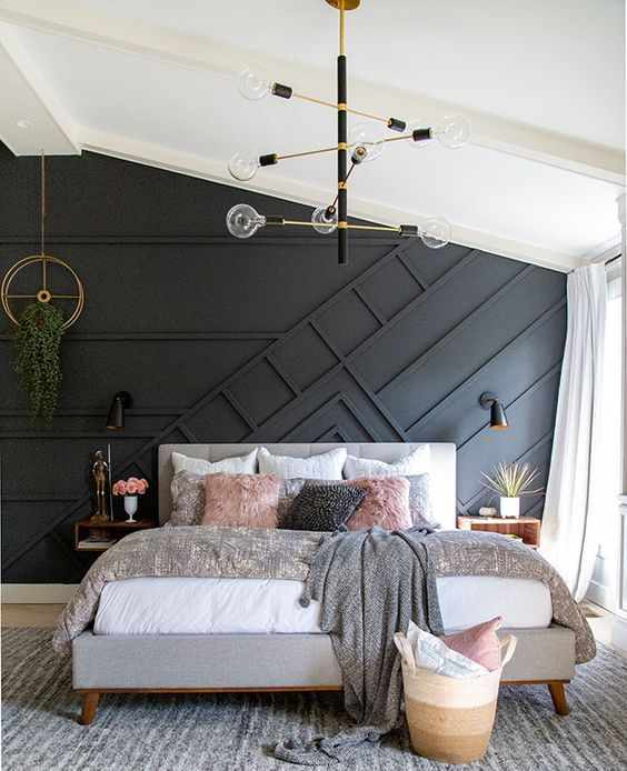 a gorgeous mid-century modern bedroom with a black paneled accent wall, a grey upholstered bed, neutral bedding, a chic chandelier, potted greenery annd a basket