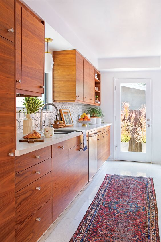 a gorgeous mid-century modern kitchen with rich-stained cabinets, a geometric backsplash and neutral stone countertops, a boo rug