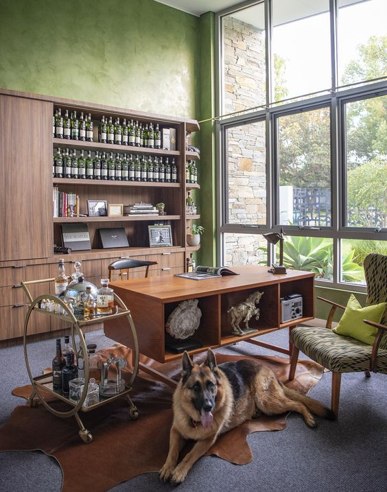 a green mid-century modern home office with a glazed wall, a rich-stained storage unit, a matching storage desk, a green and a black chair and a bar cart