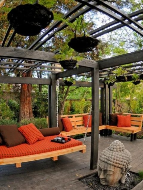 a hanging outdoor daybed with lots of pillows plus a matching built-in bench and Asia-style decor around for a zen space