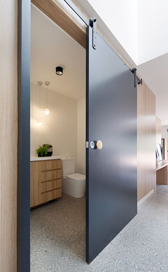 a heavy navy modern sliding door that hides a mudroom and adds a cool color accent to the space at the same time