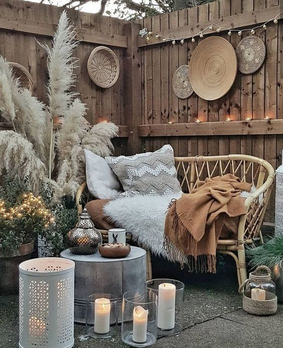 a hippie style outdoor space with a rattan sofa, pampas grass, a metal table and candle lanterns, woven decorative plates