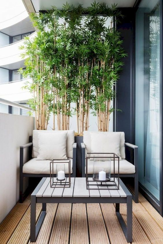 a laconic balcony in modern style, with bamboo, a couple of neutral chairs, a coffee table with candle lanterns is a cool idea