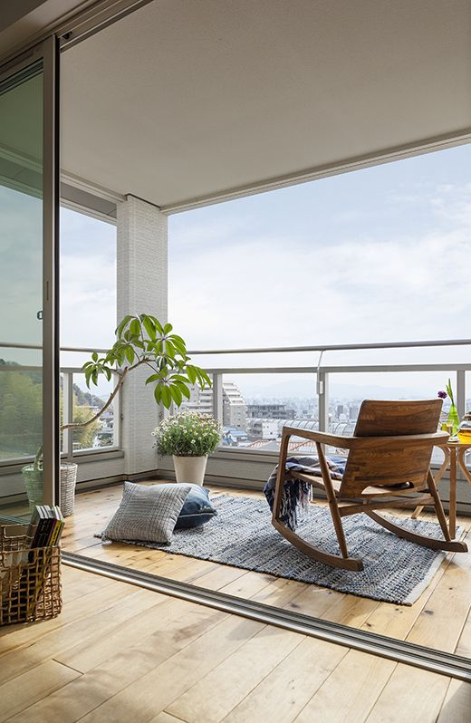 a laconic modern balcony styled with a wooden rocker, a side table and some pillows and potted plants is a cool space