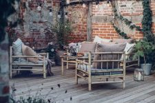 a laid-back deck with simple bamboo furniture, muted color pillows, potted greenery, string lights and candle lanterns