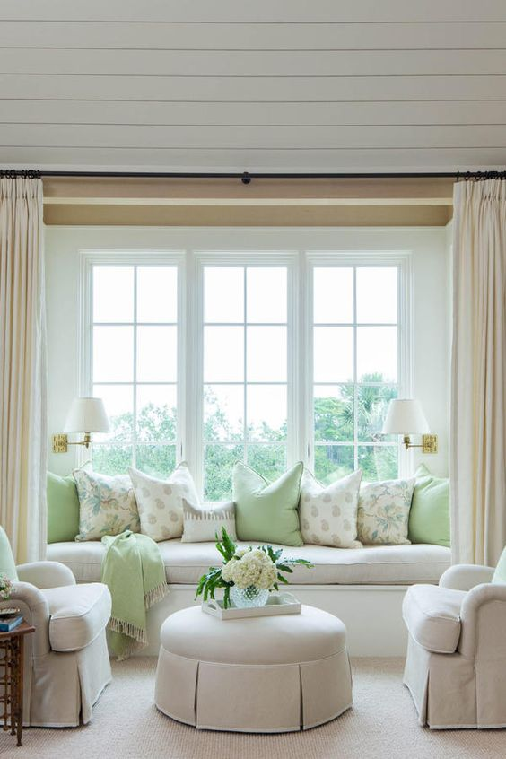 a large French window with a built-in daybed and printed pillows, chic neutral furniture, sconces and blooms for an elegant space