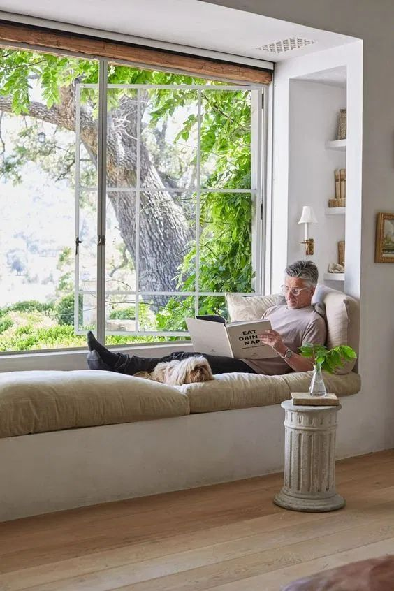 a large French window with a built-in daybed and shelves, with sconces and a refined side table make up a gorgeous nook
