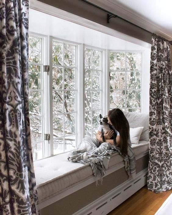 a large bow window with French windows, printed curtains, neutral bedding is a gorgeous nook to relax and spend time in