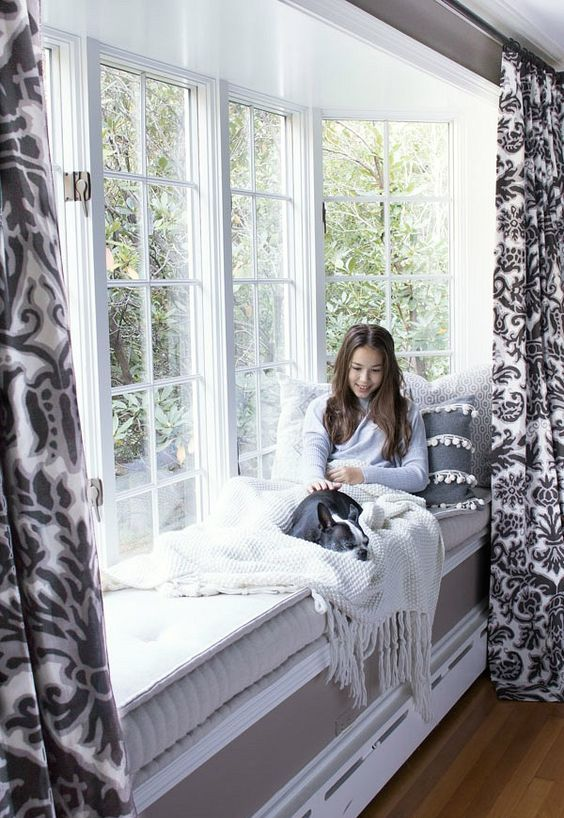 a large bow window with a built-in windowsill daybed, with neutral and muted-colored textiles and printed curtains
