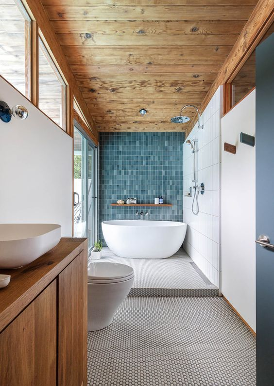 a large mid-century modern bathroom with a wooden ceiling, a penny tile floor and a blue accent wall, a stained vanity and white appliances
