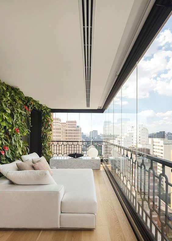 a large modern balcony with a living wall, a creamy sofa with pillows, a stone side table with quirky lamps is a very elegant and chic space