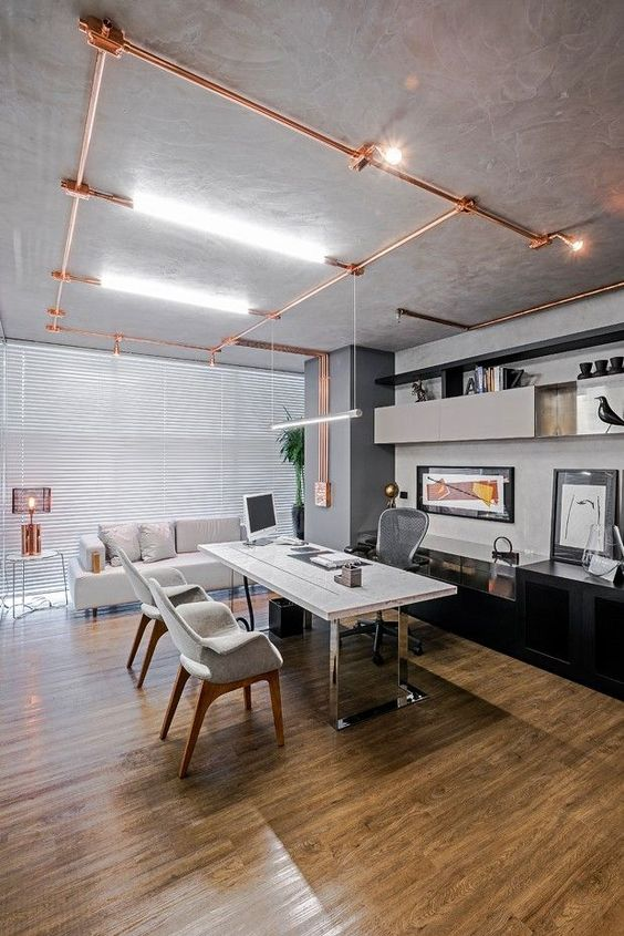 a large modern industrial home office that features exposed copper pipes, a large desk with chrome legs and a copper table lamp and they all look nice together