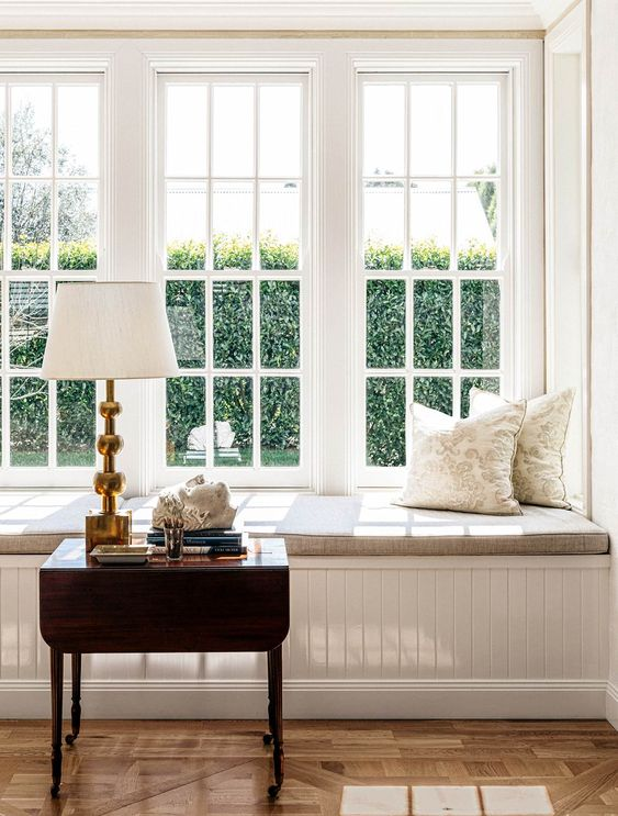 a large white French window with an elegant daybed, printed pillows, a dark stained table and a table lamp create a lovely space