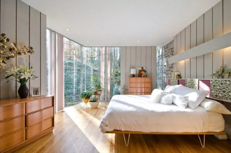 a light-filled mid-century modern bedroom with a glazed wall, stained furniture, a hairpin leg bed, potted plants and blooms