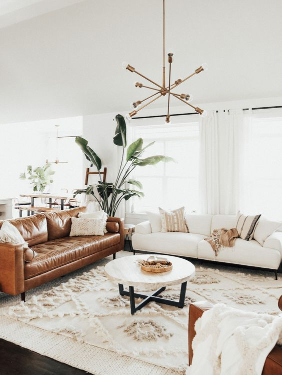 a light-filled mid-century modern living room with a creamy and amber leather sofa, a round table, a boho rug and a chic chandelier