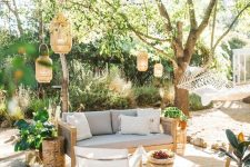 a light-filled outdoor space with wooden furniture, neutral upholstery, candle lanterns and statemrnt plants around welcomes