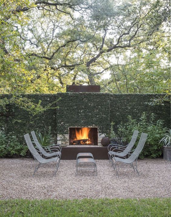 a lightweight terrace with a fireplace, pretty metal chairs and footrests and lots of climbing plants covering the wall and fireplace
