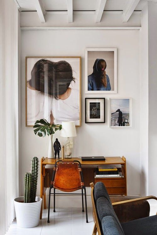 a little and chic mid-century modern working nook with a stained desk, a leather chair, a cool gallery wall, potted plants and a cool lamp