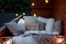 a little boho balcony with a mattress and lots of pillows, candle lanterns and string lights over the space is a gorgeous nook to relax in