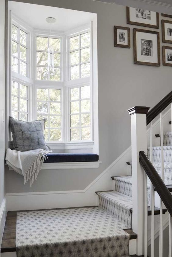 a little bow window on the stairs, with a windowsill seat, a pillow and a blanket is a very cozy nook to spend some time here