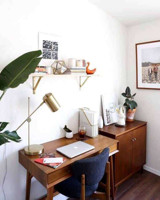 a little mid-century modern home office nook with a stained desk, a storage cabinet, a navy chair, a shelf, a gold lamp and potted plants