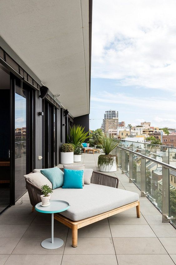 a long modern balcony wiht a sofa in the corner, statement plants in pots, a daybed with lots of pillows and a small side table is chic