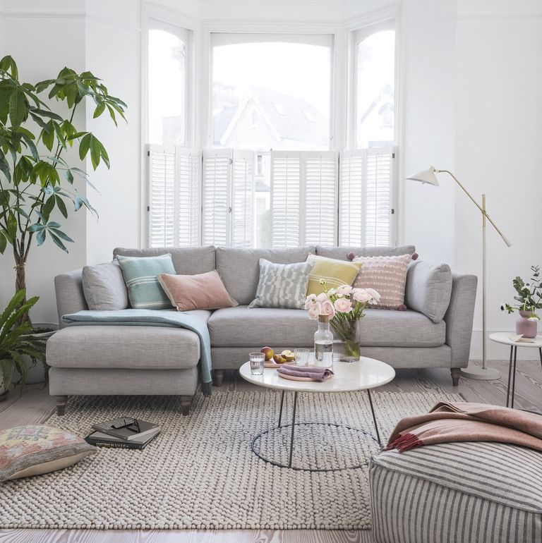 a lovel modern living room with a bow window, a grey sectional, pastel pillows, a round table and an ottoman plus potted plants