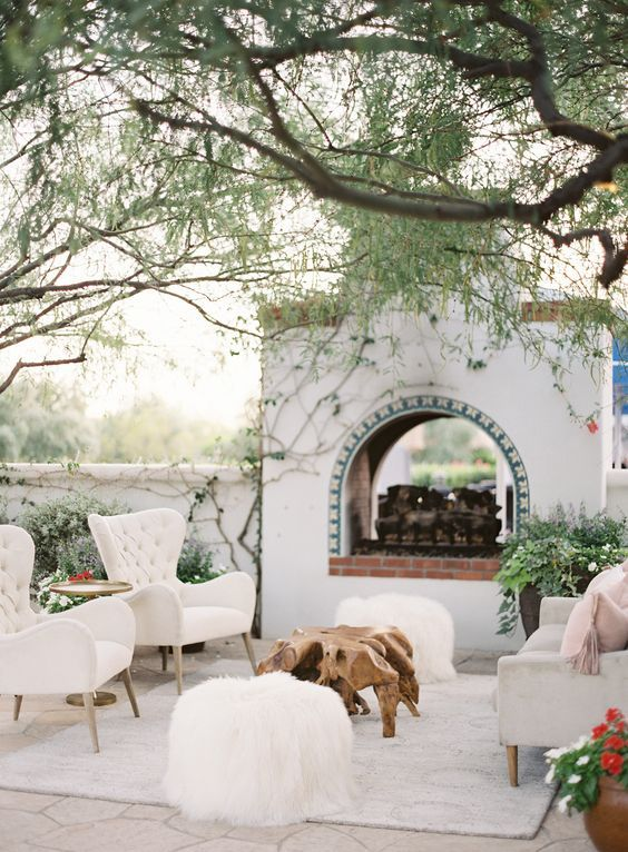 a lovely Mediterranean terrace with a gorgeous fireplace with maosic tiles and bricks, white furniture, a sriftwood table and fluffy poufs