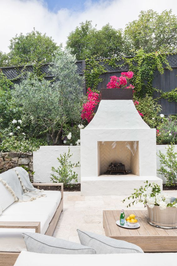 a lovely Mediterranean terrace with a stucco fireplace, neutral furniture, a light stained coffee table and lots of greenery and blooms