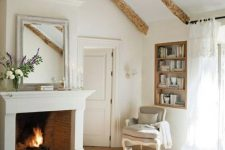 a lovely Provence bedroom with a fireplace, a large bed, a vintage chair and ottoman, a built-in bookshelf, wooden beams and floral textiles