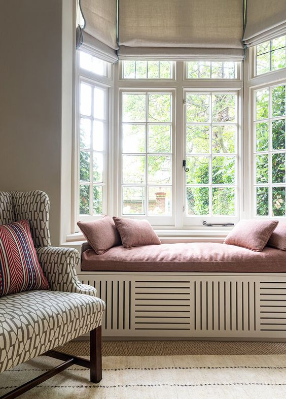 a lovely and cozy space with a bow window finished wiht a built-in daybed, with dusty pink bedding and some shades
