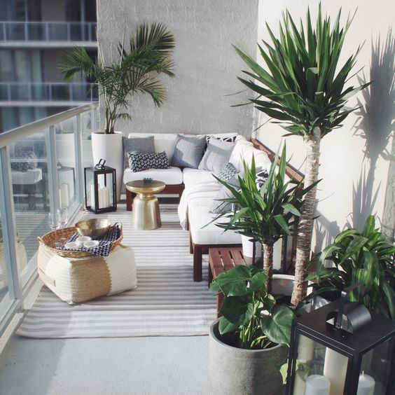 a lovely and welcoming balcony with a rich-stained wooden bench with white upholstery, potted plants, a small pouf and a striped rug