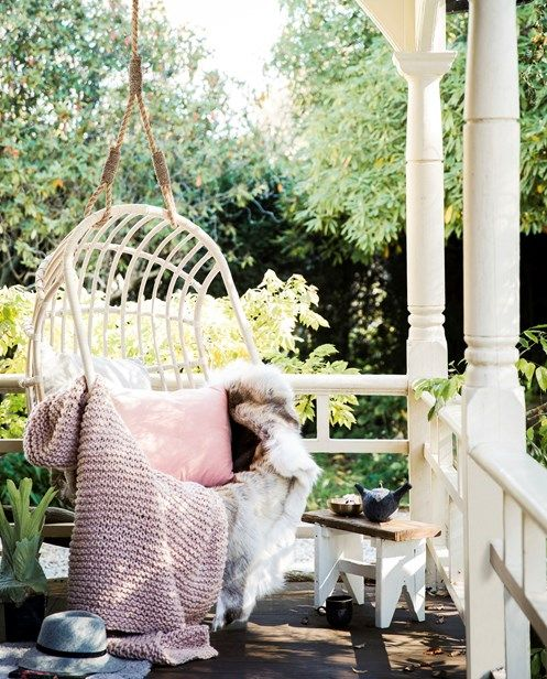 a lovely back porch with a rattan hanging chair with cool blankets and pillows, a small side table and lots of fresh greenery around