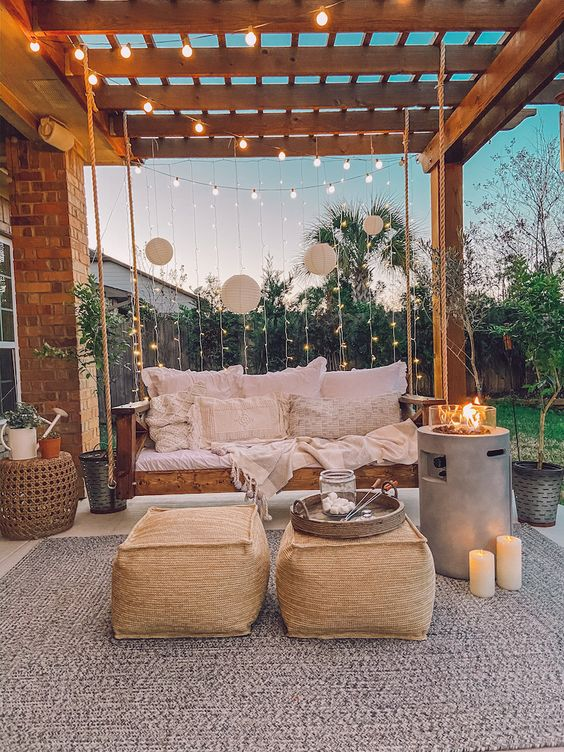 a lovely back boho porch with a wooden hanging daybed, some neutral pillows, a duo of poufs, a fire pit and some candles and string lights
