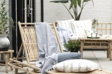 a lovely bamboo lounger with neutral and pastel pillows, a matching stool and a tray for a relaxed tropical outdoor space