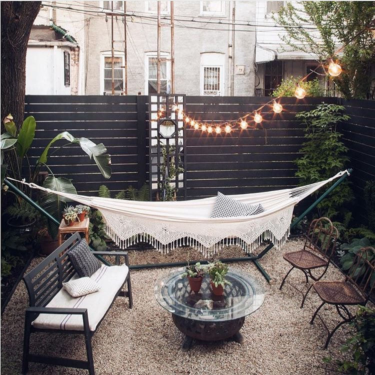 a lovely boho space with lots of greenery, a beautiful hammock, vintage garden furniture, a glass coffee table and string lights