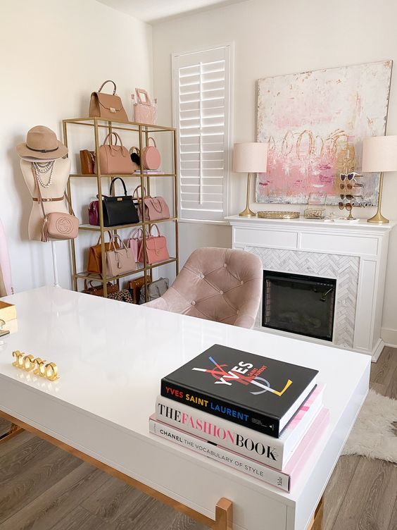 a lovely cloffice with a marble clad fireplace, a pretty artwork, a stand with beautiful bags, a desk and a blush chair is amazingly girlish