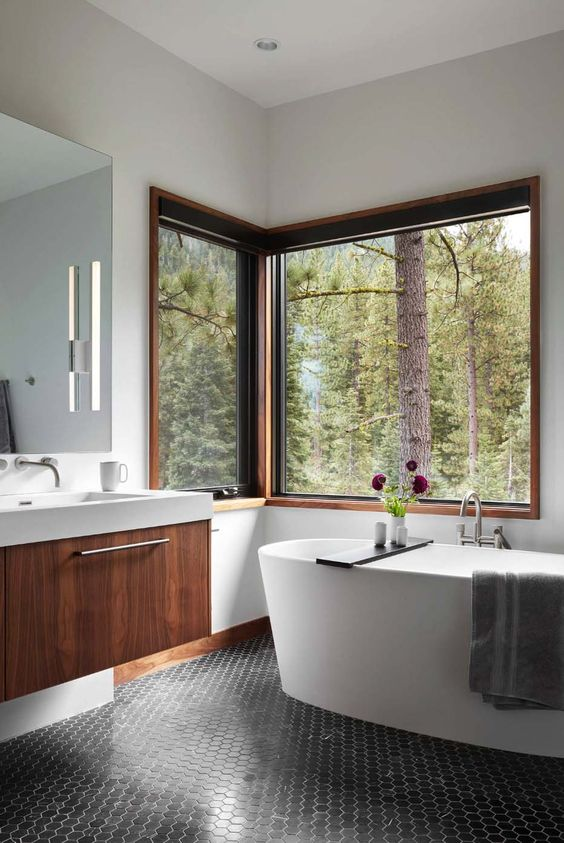 a lovely contemporary bathroom with a corner window, an oval tub, black penny tiles and a floating vanity