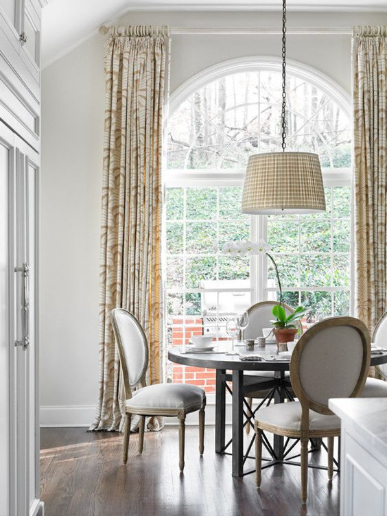 a lovely dining room with an oversized French window, a round table and rounded chairs, a pendant lamp and printed curtains