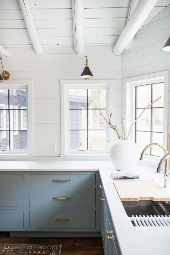 a lovely farmhouse kitchen with light blue cabinets, gold handles and gold sconces, chromatic fixtures looks very harmonious and serene