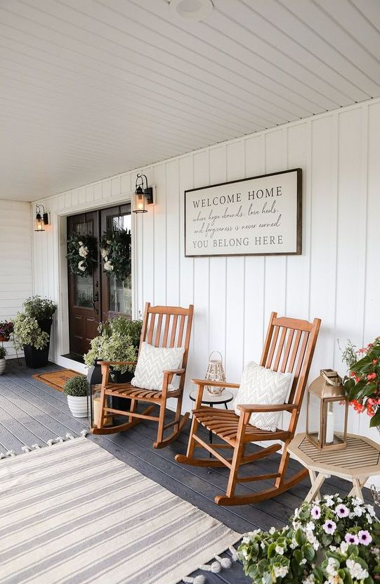 a lovely farmhouse porch styled for summer, with potted greenery, blooms, stained rockers, a candle lantern and a striped rug