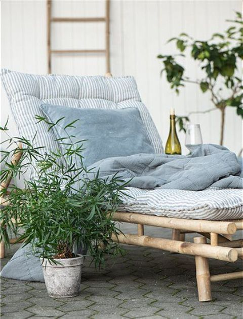 a lovely lounger of bamboo with printed blue bedding and a mattress, potted greenery is a very cool idea for an outdoor space